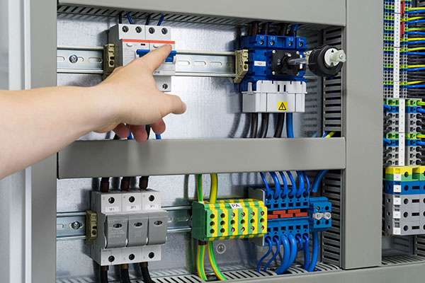 Hand eines Elektrikers zeigt auf eine Sicherung in einem Schalts